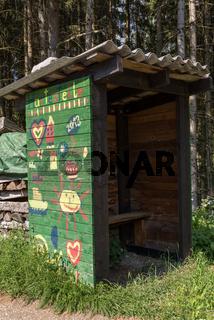 Von Kindern bemalte Bushaltestelle am Waldrand - Holzhütte und Wartehäuschen