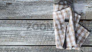 Fork and checkered napkin on wooden table.