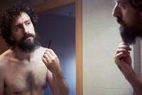 Middle-aged hispanic man cutting his beard