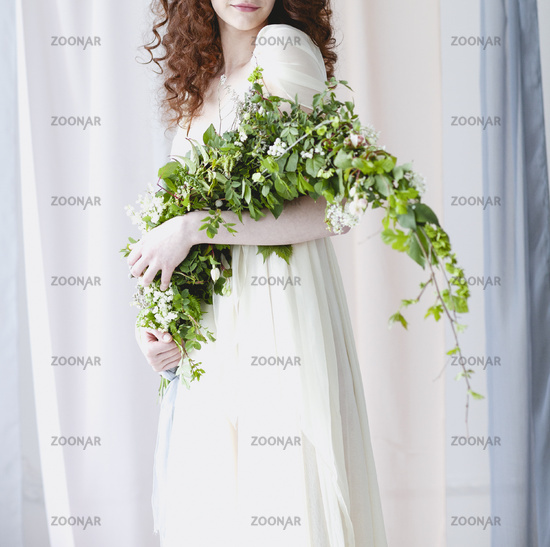 Bride in delicate gown with unusial bouquet of small white flowers