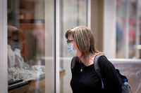 Woman goes window-shopping with a protective mask because of existing mask requirement