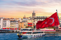 Karakoy pier, a ferry, Turkish flag and the Galata Tower in the background, Istanbul, Turkey
