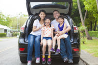 happy family sitting in the car and their house be
