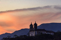 Old and historic 18th century church with its facade illuminated by sunset