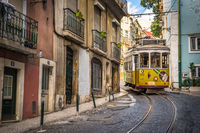 LISBON, PORTUGAL - July 1, 2018: Vintage tram in the narrow street of Alfama district in Lisbon.