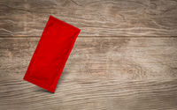 Blank Red Condiment Packet Floating on Aged Wood Background