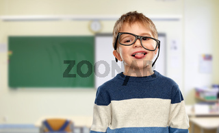 little boy in glasses showing tongue at school