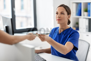doctor and patient with credit card at hospital