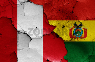 flags of Peru and Bolivia painted on cracked wall