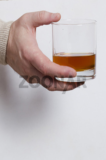 Hand with a glass of whiskey