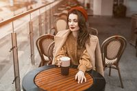 All thoughtful in memories young Parisian woman sitting outdoors restaurant terrace looking away holding a coffee mug. Portrait of stylish young woman wearing autumn coat and red beret outdoors