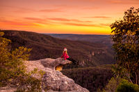 Hiker sitting on edge of rock precipice with escarpment valley views