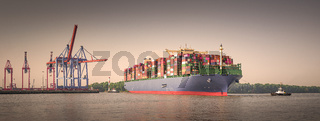 Panorama of a large container ship in Hamburg at sunrise