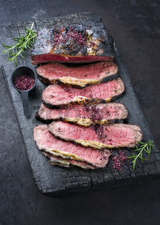 Traditional Commonwealth Sunday roast with sliced cold cuts roast beef with herbs and salt as top view on a rustic charred wooden board