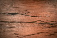 Wooden board with dark cracks close-up. Background image of wooden coating. High quality photo