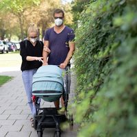 Worried young parent walking on empty street with stroller wearing medical masks to protect them from corona virus. Social distancing life during corona virus pandemic