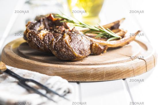 Grilled lamb chops on cutting board.