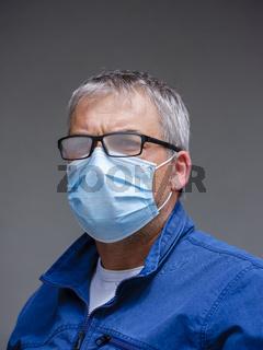 Mann mit angelaufener Brille durch die Mundschutzmaske