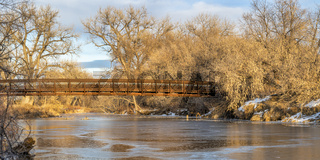 footbridge over frozen river -  Poudre River Trail