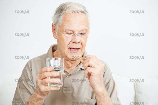 Senior schluckt Tablette mit Wasser