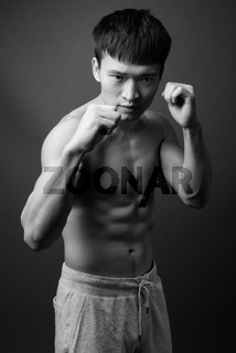 Portrait of young muscular Chinese man shirtless