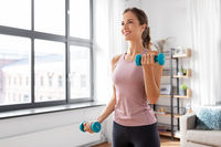 smiling young with dumbbells exercising at home