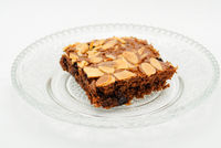 Chocolate brownie with almond topping on glass plated