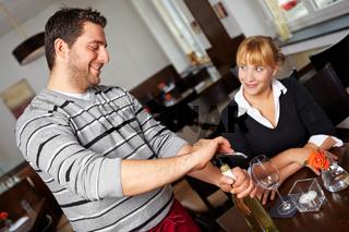 Weinkellner öffnet Weinflasche im Restaurant