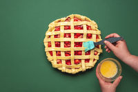 Making a strawberries tart. Greasing with egg yolk the pie.