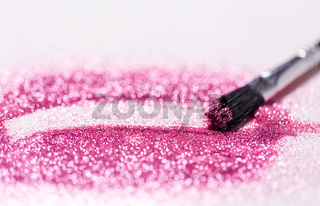 make up brush making stroke on pink glitters