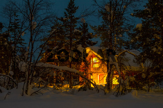 Night Snowy Forest and Illuminated Wooden Cottage
