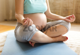 Young pregnant woman meditating while sitting in lotus position