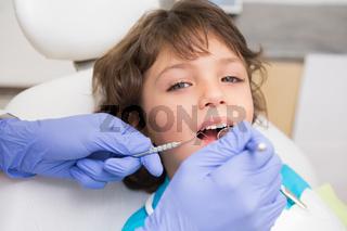 Pediatric dentist examining a little boys teeth in the dentists chair
