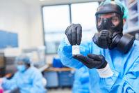 Forscher im Labor mit Ampulle Covid-19 Impfstoff