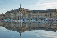 People have fun and refresh on a hot summer day in the mirror fountain in Bordeaux, France
