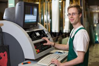 glazier craftsman in workshop operating a cutting machine