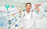 asian female doctor with medicine at pharmacy
