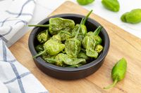 Cooked Padron peppers in a a bowl on wooden table