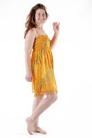 Smiling young woman in yellow dress stands barefoot against white background