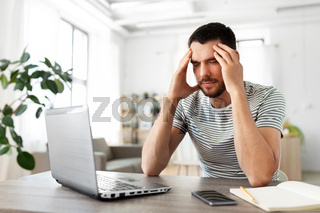 stressed man with laptop working at home office