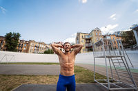 Muscular guy with a naked torso in outdoor street gym.