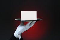 Closeup of a white gloved hand holding a blank note on a silver tray. Horizontal format on a light t