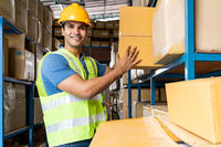 Indian warehouse worker put cardboard box in shelf