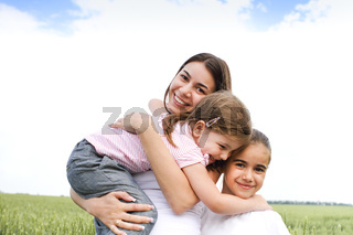 Satisfied mother embracing with daughters