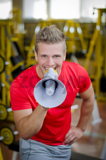 Personal trainer in gym yelling with megaphone towards camera