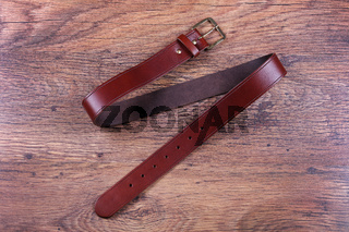 Brown leather belt on a wood background