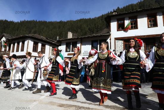 People in traditional costumes dance Bulgarian horo in Shiroka laka, Bulgaria