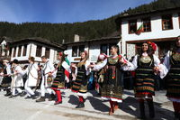 People in traditional costumes dance Bulgarian horo in Shiroka laka, Bulgaria