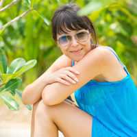Close-up Portrait of young pretty woman with the blue dress and sunglasses sitting of the green tropical forest