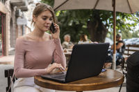 Woman working on laptop at office while talking on phone, backlit warm light. Portrait of young smiling business woman calling her best friend, having break, telling something funny, sitting in cafe.
